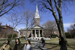 In this Sunday, March 13, 2016, photo people walk near Memorial Church, behind, on the campus of Harvard University, in Cambridge, Mass. Amid scrutiny from Congress and campus activists, colleges across the country are under growing pressure to reveal the financial investments made using their endowments. (AP Photo/Steven Senne)