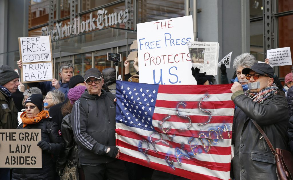 "ADVANCE FOR USE SUNDAY, MARCH 12, 2017 AND THEREAFTER-FILE - In this Sunday, Feb. 26, 2017 file photo, demonstrators stand with U.S. flags and signs in a show of solidarity with the press in front of The New York Times building in New York. The White House banned several major news outlets, including The New York Times and CNN, from an off-camera briefing, known as a ""press gaggle,"" two days earlier. (AP Photo/Kathy Willens)"