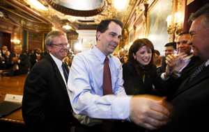 ADVANCE FOR USE SUNDAY, MARCH 13, 2016 AND THEREAFTER - FILE - In this June 6, 2012 file photo, Wisconsin Gov. Scott Walker, second from left, and Lt. Gov. Rebecca Kleefisch are greeted by the governor's cabinet and staff at the state Capitol Madison, Wis., a day after Walker beat Milwaukee Mayor Tom Barrett in a recall election. A railroad executive was caught violating contribution limits for illegally funneling cash to Walker's campaign through his employees. Key to the investigation, was a requirement that donors disclose where they work, but Republican lawmakers have since wiped out the rule. (AP Photo/Andy Manis, File)